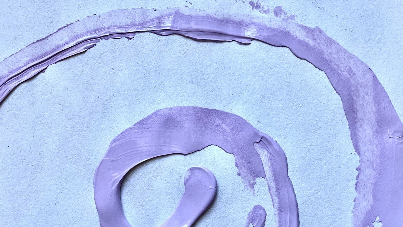 This is an image with blue undertones of a partially obscured swirl of pink paint on a textured white background.