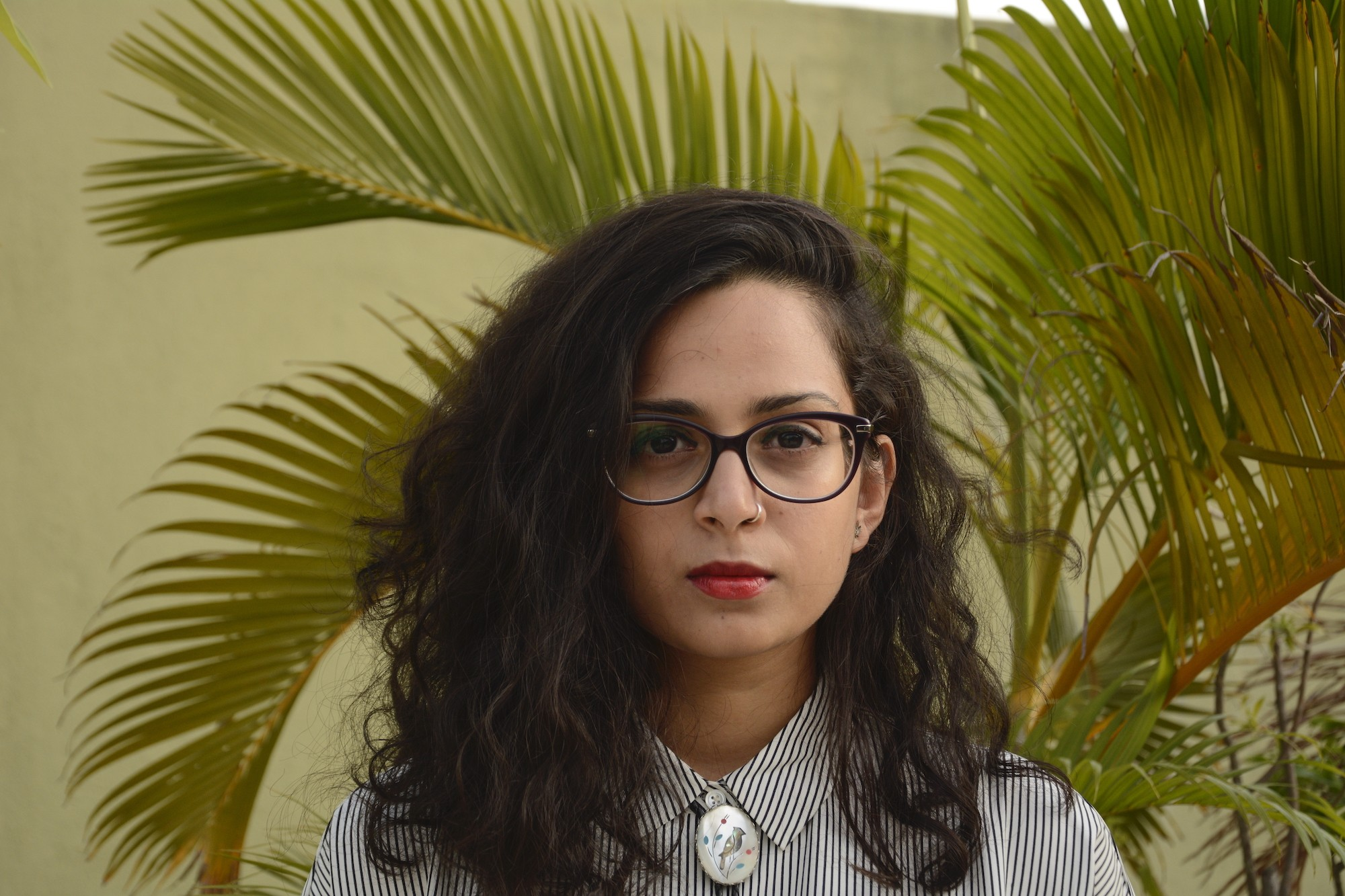 Aditi Machado stands in front of an areca palm, wearing red lipstick and black frame glasses.