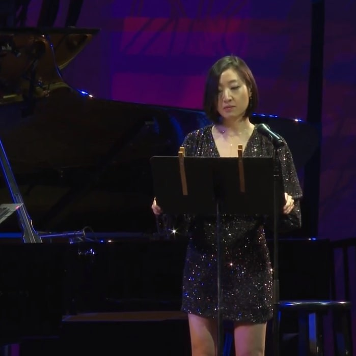 Cindy Tran stands on a stage at music stand in front of a grand piano, wearing a black sparkly dress