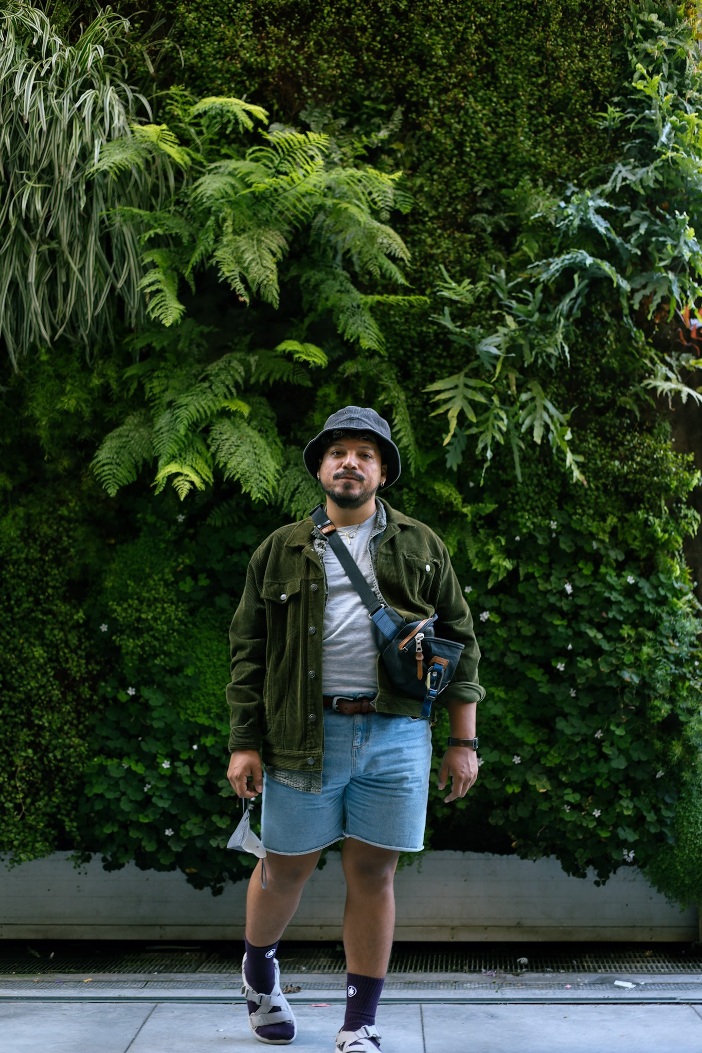 Cristóbal Guerra stands in front of a wall of verdant foliage, looking into the camera, wearing a blue bucket hat
