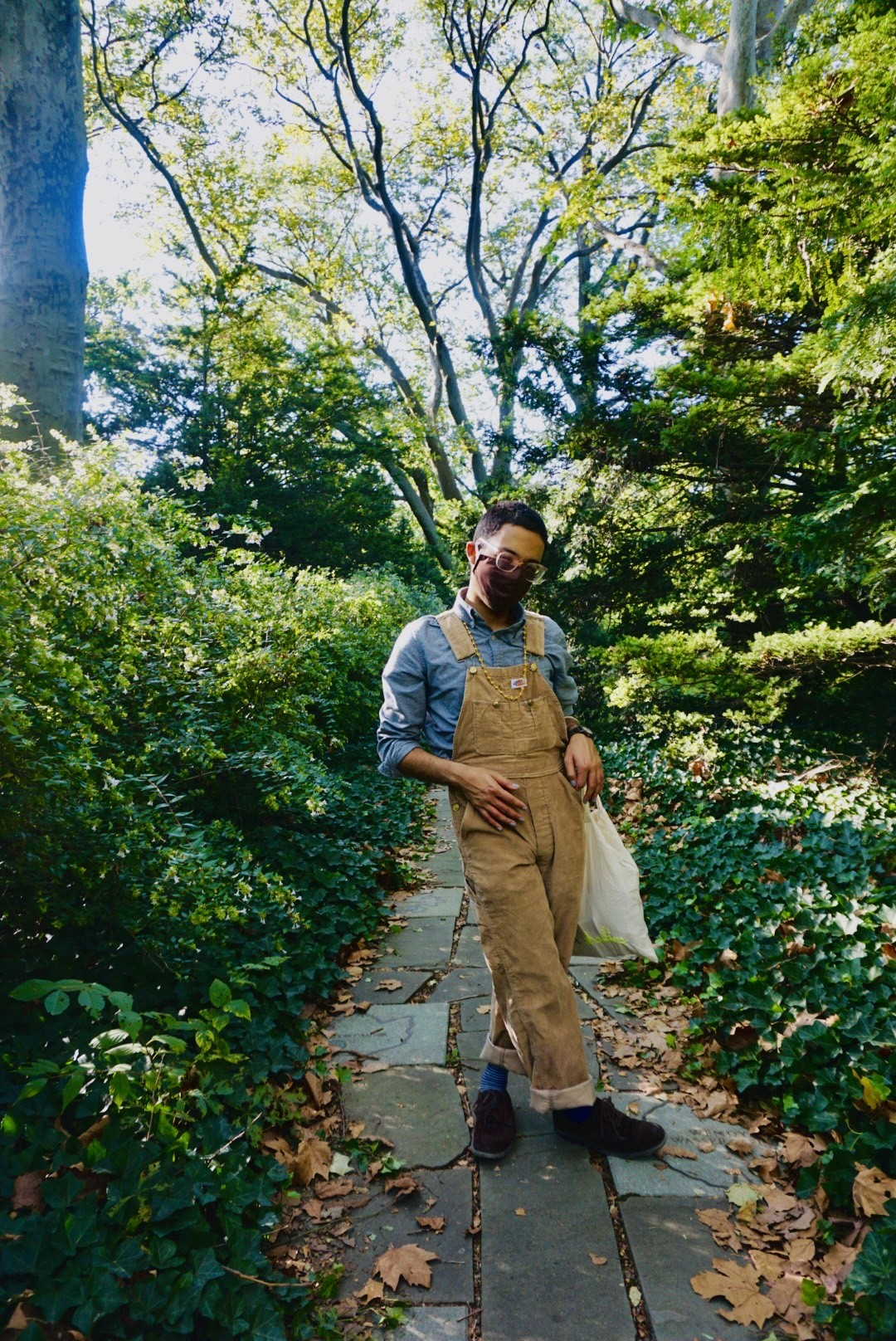danilo machado is standing outside on a cobblestone path surrounded by green plants, wearing overalls and a face mask.
