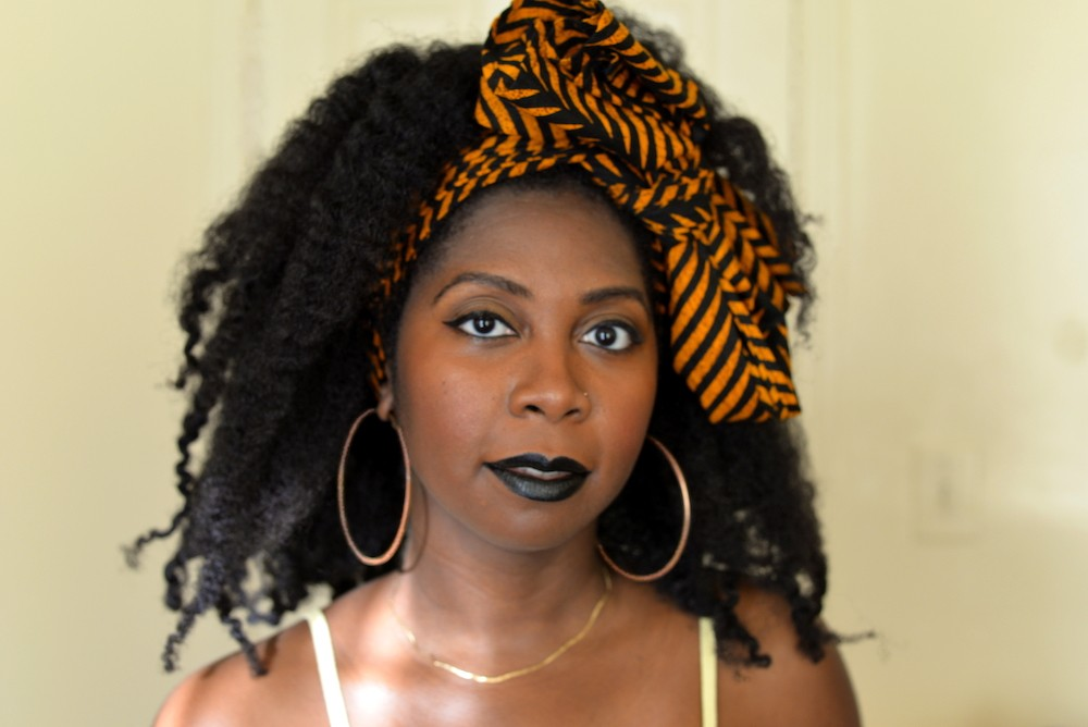Desiree C. Bailey faces the camera, wearing dark lipstick and smiling