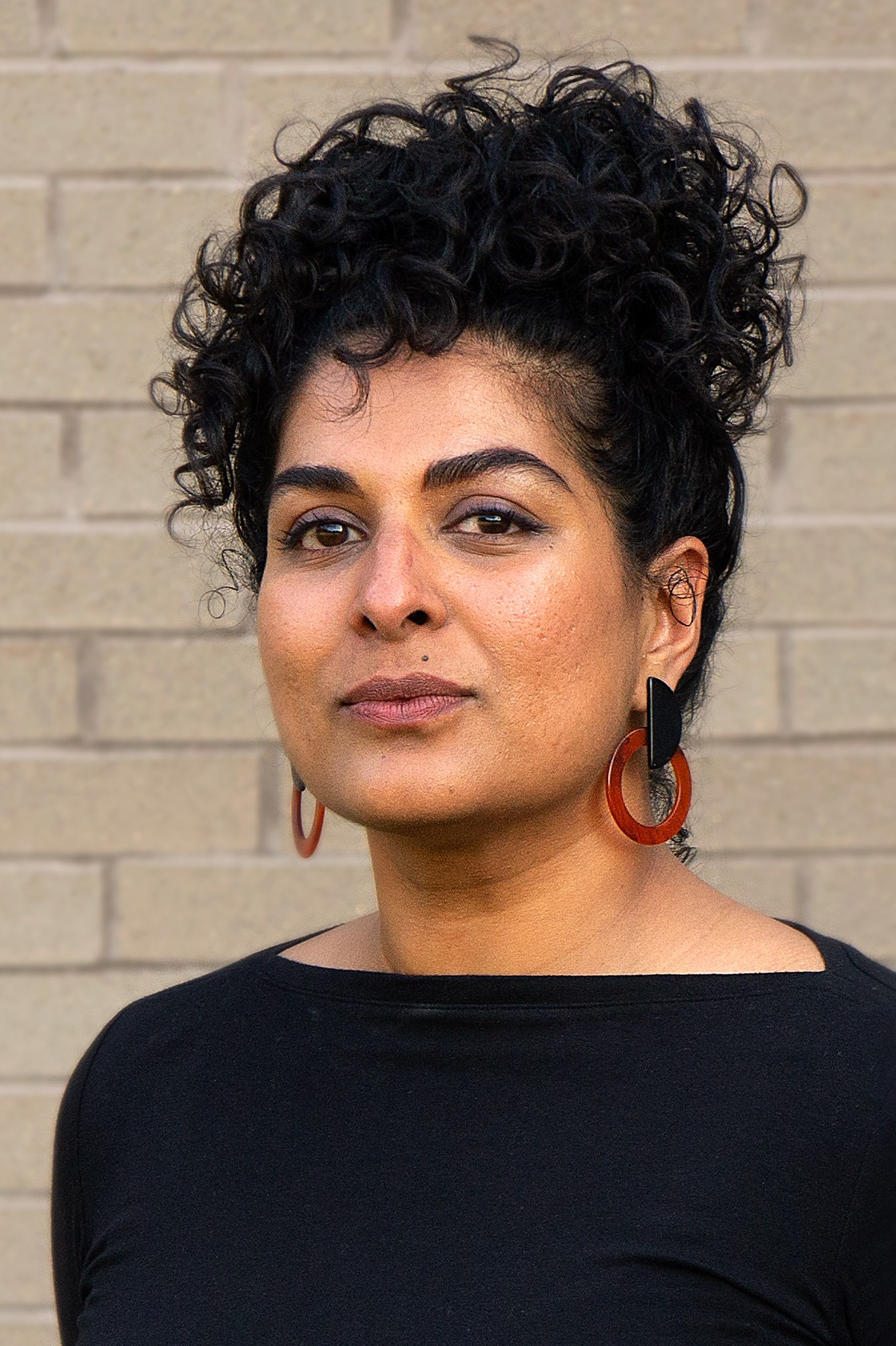 Divya Victor faces the camera in front of a brick wall, wearing a black shirt and red hoop earrings.