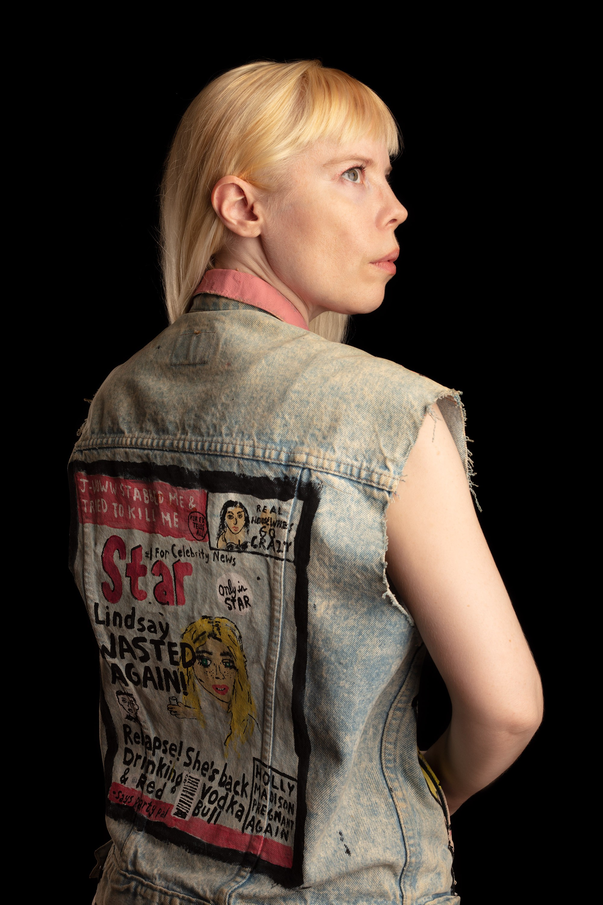 Kate Durbin is standing facing away from the camera, with her face visible in profile, wearing a cutoff denim vest with an illustrated tabloid cover on the back.