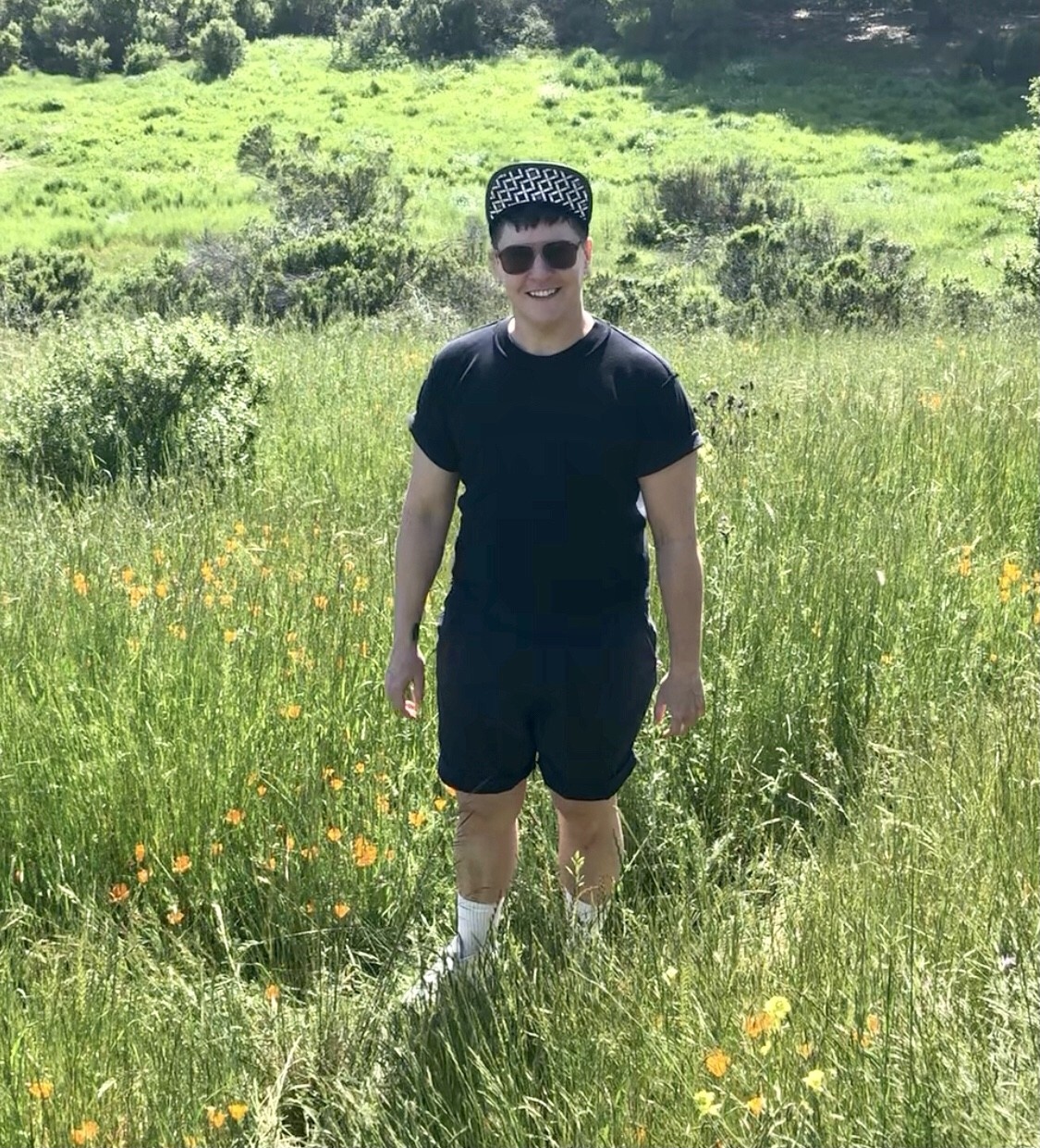 Maxe Crandall stands in a field of wildflowers, looking at the camera and smiling, wearing all black with a black and white cap.