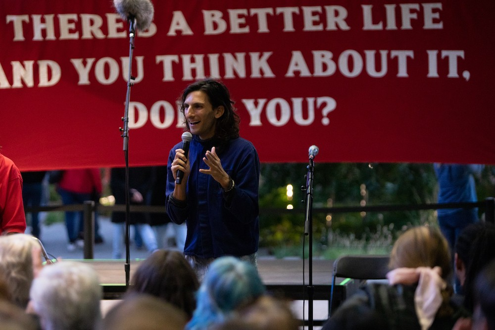 """Morgan Bassichis is holding a microphone, speaking to a crowd. They are standing in front of a banner, which is partially blocked from you. The legible part reads, """"THERE'S A BETTER LIFE / AND YOU THINK ABOUT IT / DON'T YOU?"""""""