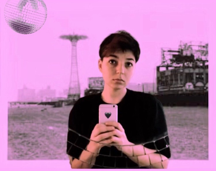 NM Esc is standing in front of a pinkish-purple image of Coney Island with a disco ball in the upper left corner. They are wearing a black t-shirt, and holding an iPhone with a black heart sticker on it that they are using to take the picture.