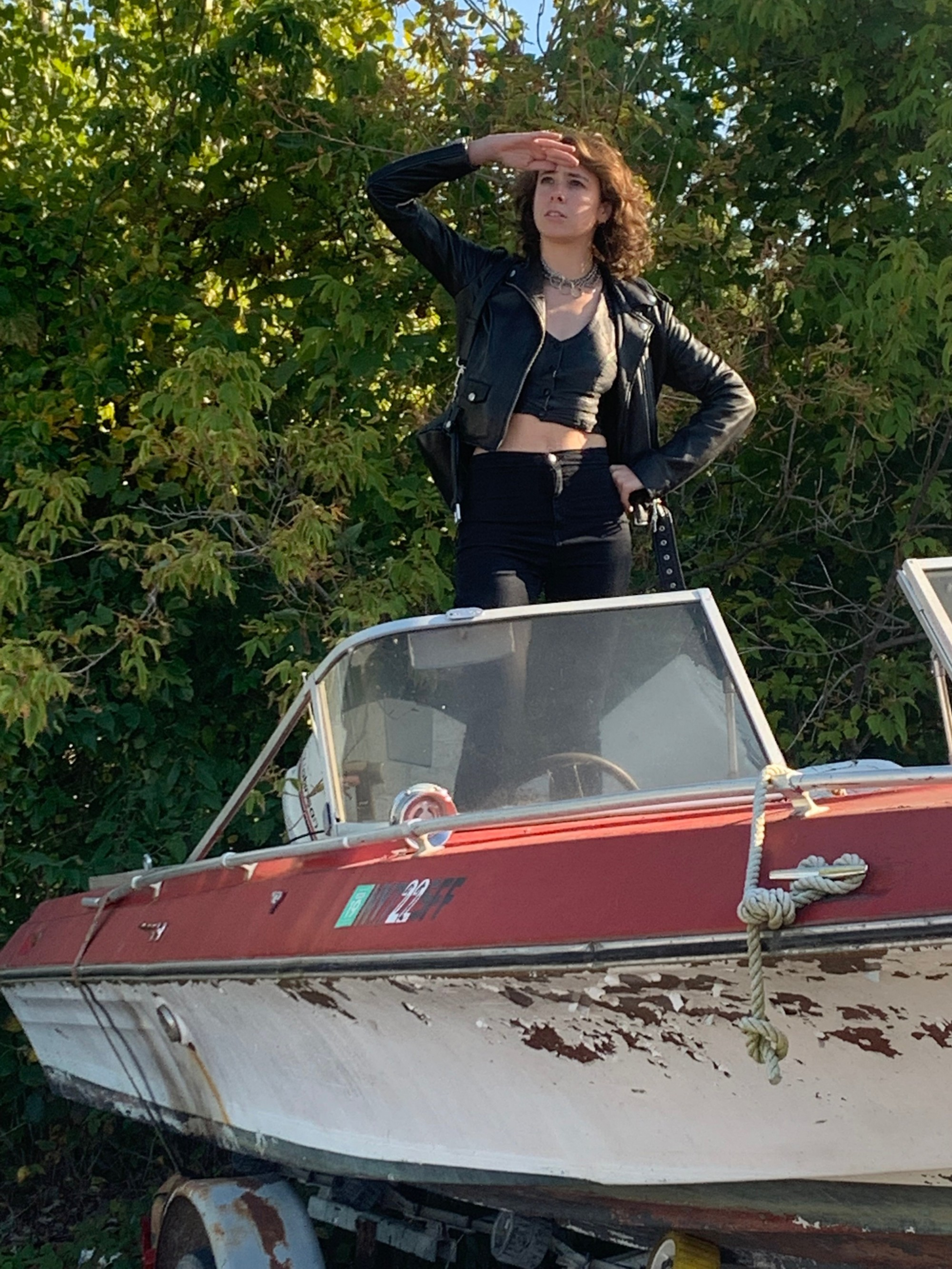 Rebecca Teich is dressed in all black, standing on a dilapidated boat parked on land, with green trees in the background, their hand raised to their eyebrows as if navigating.