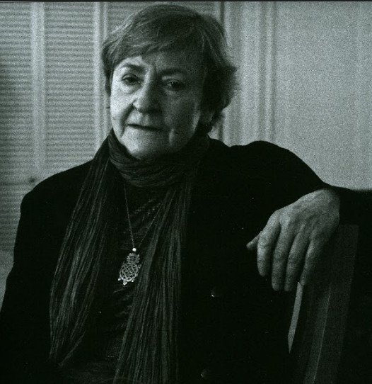 In this black and white portrait, Rosmarie Waldrop sits in a chair with her arm resting on its back, looking into the camera