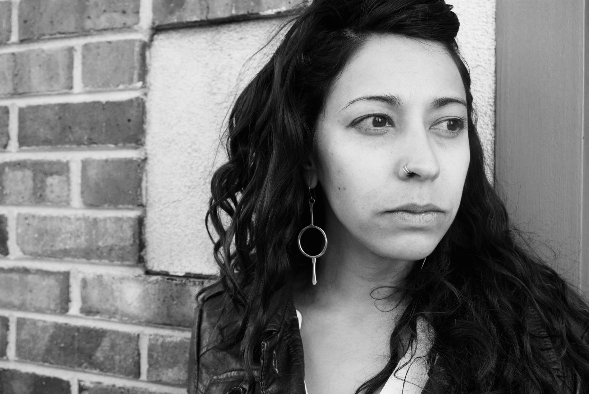 In this black and white photo, Serena Chopra is standing in front of a brick wall to the right of the frame, looking to the right.