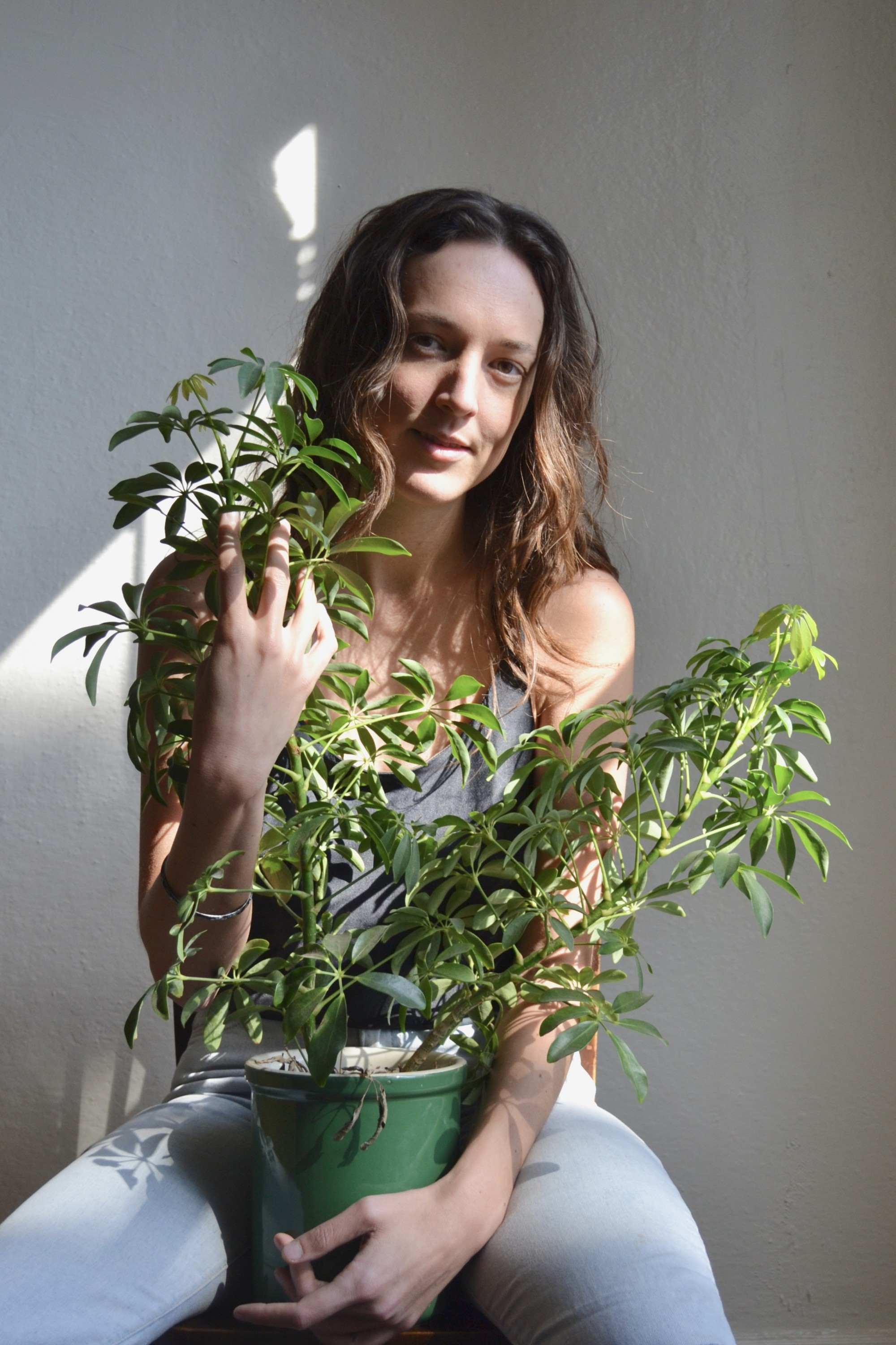 Sophia Dahlin sits in front of a white wall in a spot of light, holding a houseplant in her lap