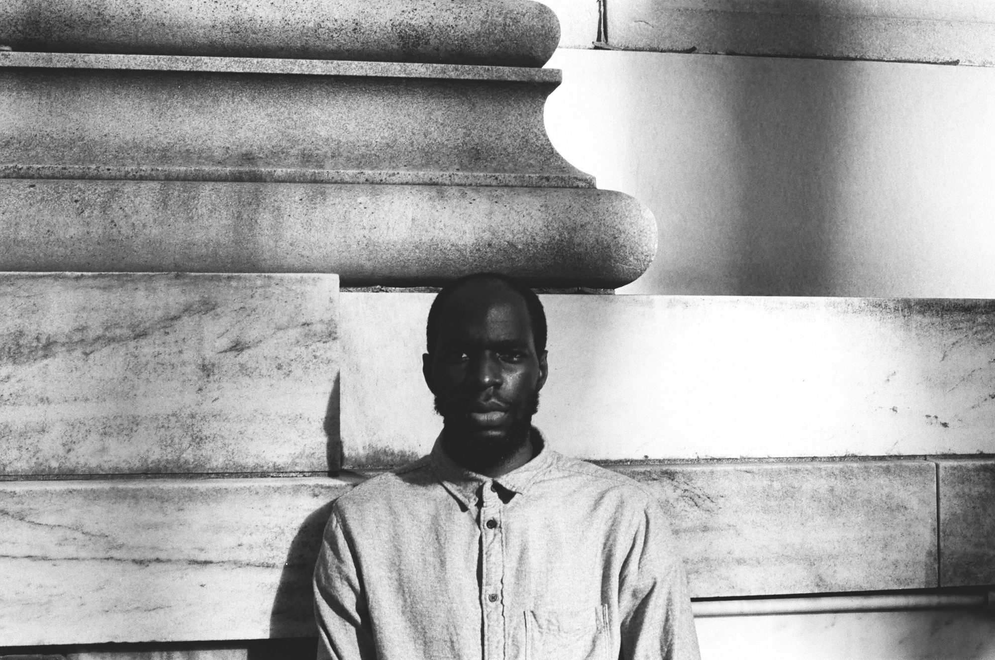 Tobi Kassim is standing in front of a large column in this black and white portrait.