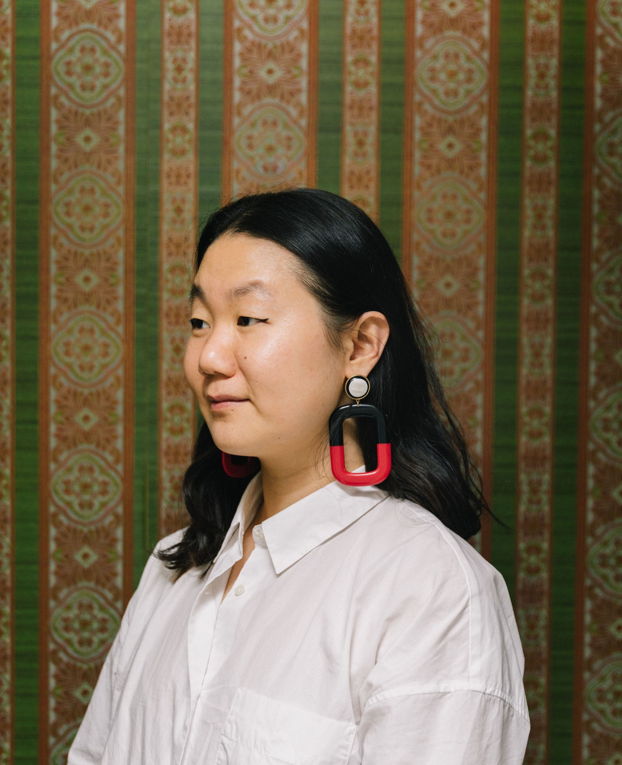 Wendy Xu stands in front of green and orange vertical striped wallpaper, wearing a white shirt and large red and black earrings, looking to the side.