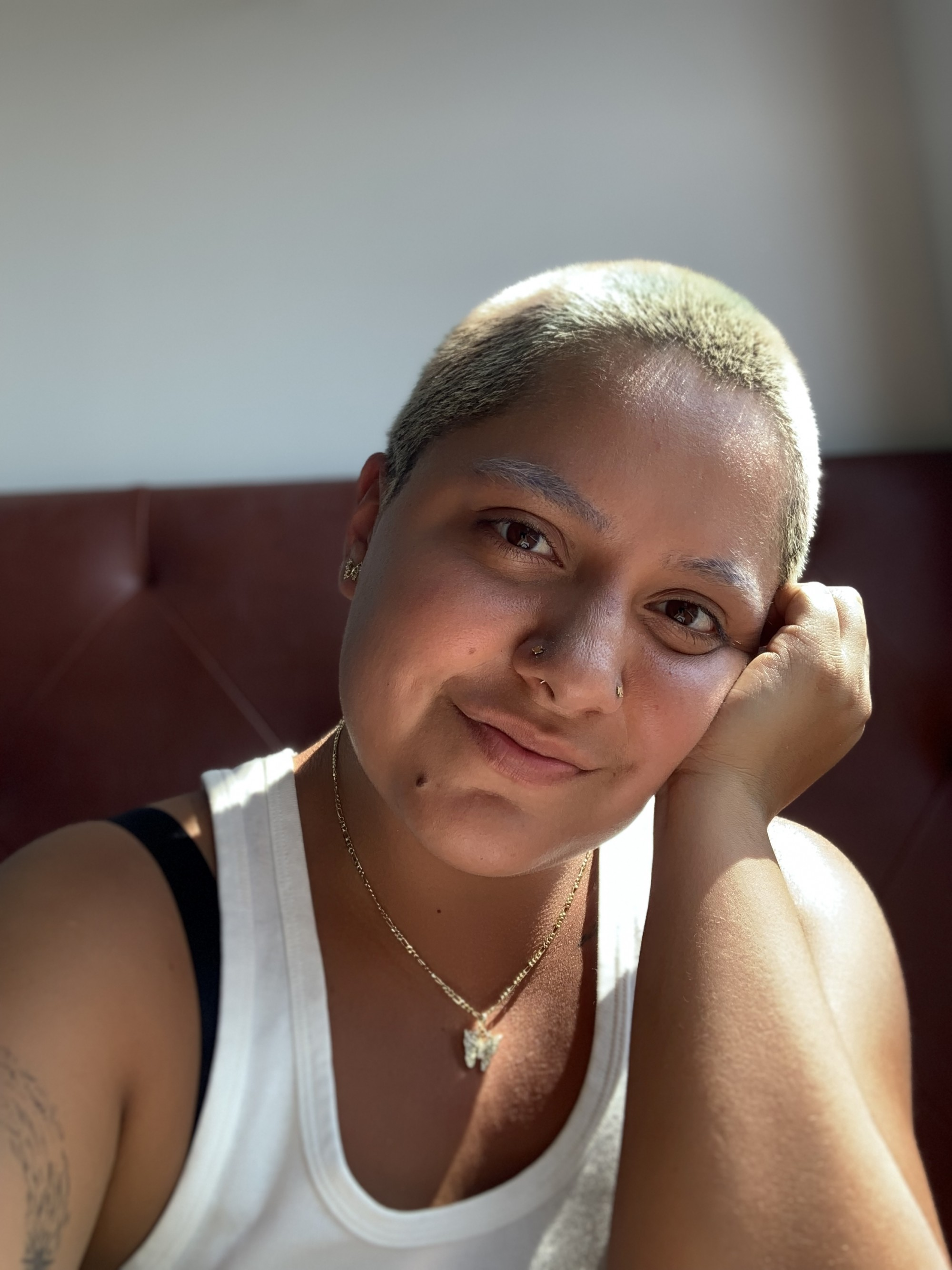 xime izquierdo ugaz faces the camera, smiling, with their head resting on their palm, wearing a white tank top, with light shining in from the side.
